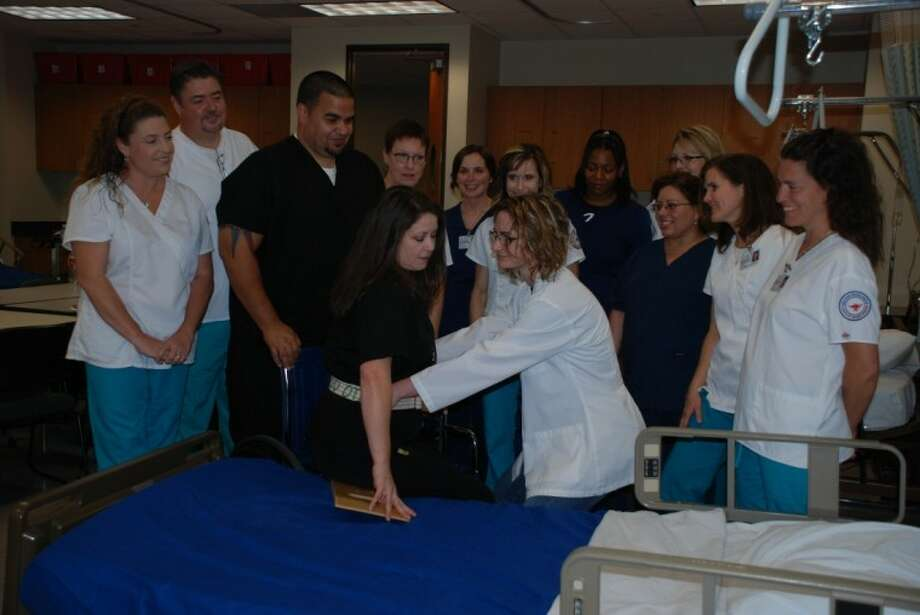 Collaboration between LSC-Kingwood's OTA and ADN departments earned both the Innovators of the Year award. OTA students Hector Toro and Lisa Maranto, center, in dark scrubs, demonstrate proper body mechanic techniques with ADN student Ashley Anderson. Watching the demonstrations are ADN students (white scrubs) Tammy Weidner, Brian Beresford, Virginia Mercado, Amy Owens, Kristy Bailey, Sandra Cason and Alisa Schumacher and OTA students Brenda Hulse, Elizabeth Robledo and Andrea JohnBaptiste.
