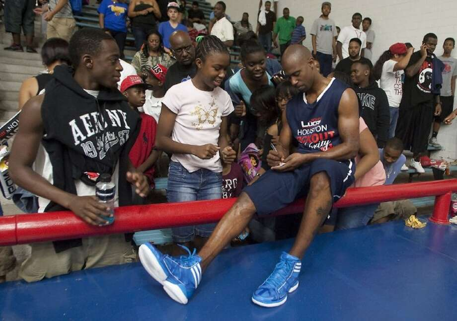 Former NBA guard T.J. Ford, a Willowridge graduate, signs autographs during the Houston Lockout Celebrity Basketball Game at Delmar Fieldhouse. Photo: HCN File Photo