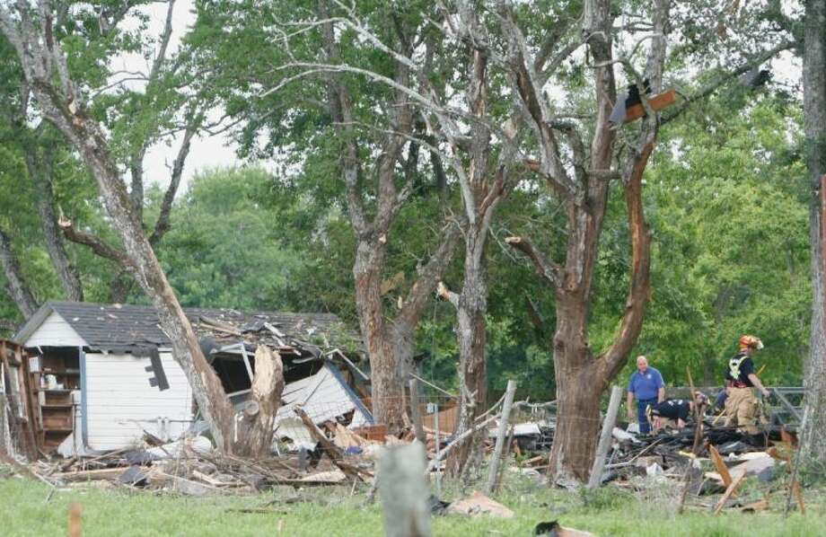 Firefighters and Montgomery County Fire Marshall officials survey the scene of an early morning home explosion Tuesday in Dobbin. Two adults and a child were transported from the home by medical helicopter. The cause of the explosion is still under investigation. Photo: Eric S. Swist