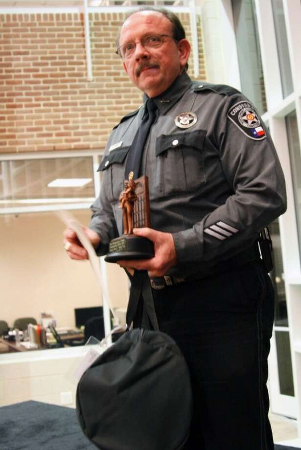 """Montgomery County Precinct 4 Constable's Deputy James E. """"Jimmy"""" Cox accepts a trophy, bag and tools as an officer of the year at the annual EMCID Law Enforcement Appreciation Dinner March 19."""