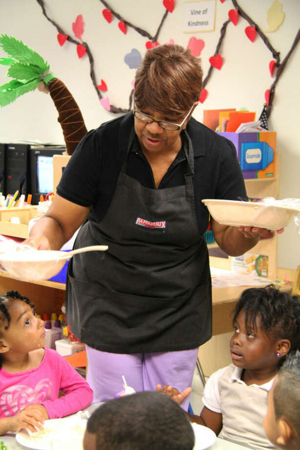 From left, HCDE Head Start chef Linda Owens serves a meal to students Jaylynn Benning and Kennedy Williams. Photo: Amanda Arnold