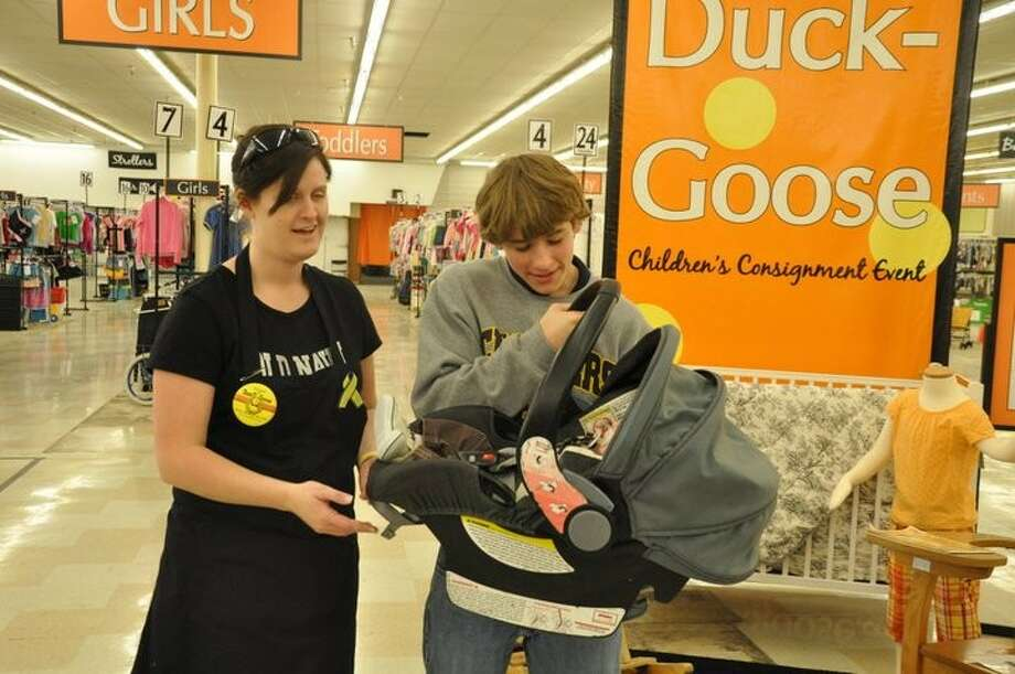 A volunteer helps a shopper try out an infant car seat at last year's Duck Duck Goose event in The Woodlands.