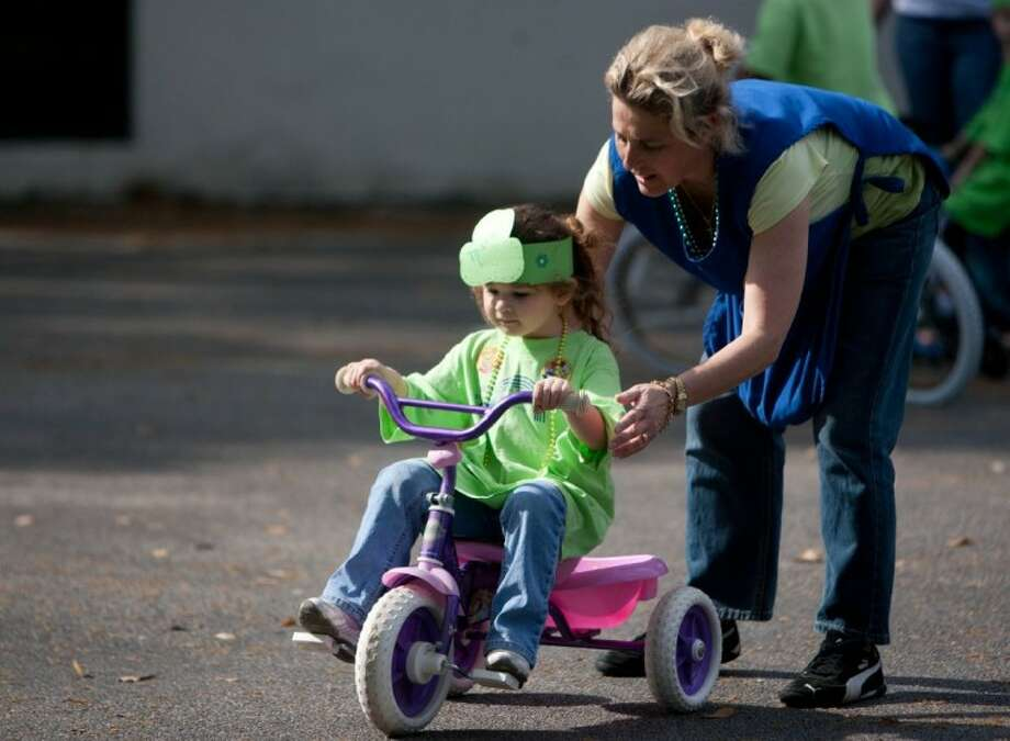 Monica Paoli, right, helps student Mara Leone during the Beginnings and Beyond daycare's eighth annual Trike-a-Thon on Friday in Spring benefitting St. Jude's Children's Hospital. Photo: Staff Photo By Eric S. Swist