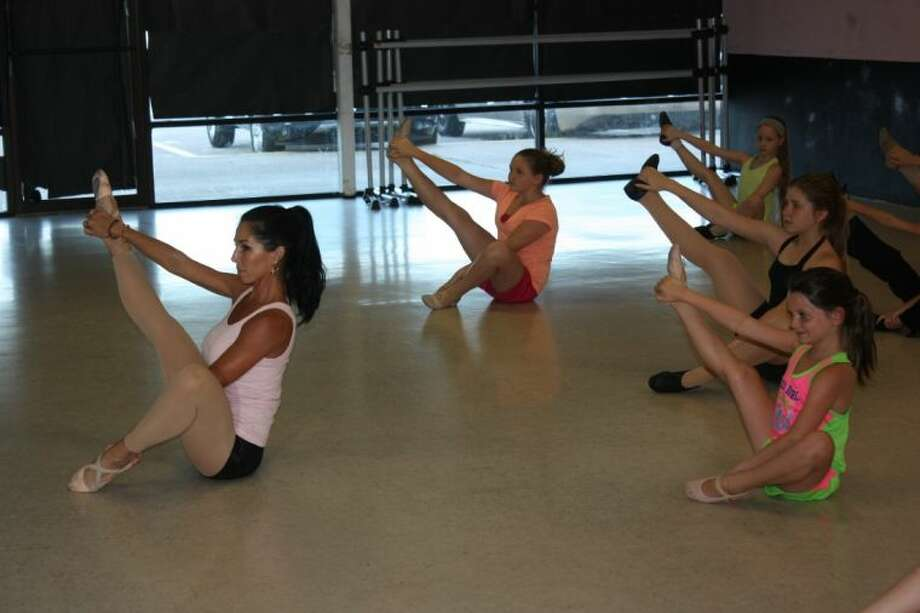 Julie Fry leads her class in warm up stretches shortly before beginning class at her new studio location in Truly Plaza in the H-E-B parking lot. Photo: RACHEL HALL