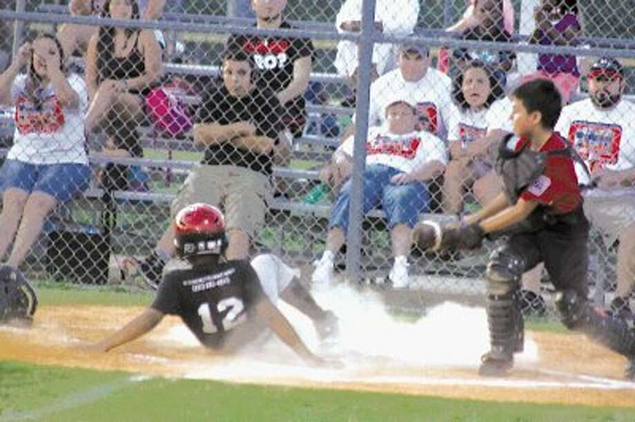 Pasadena Red's player Chris Cano (12) slides home with one of the team's runs Friday night. Looking on is North Shore catcher Davian Pastran.