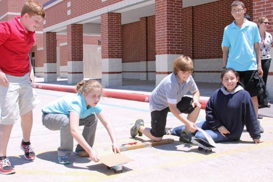 Alexander Middle School students Victoria Bedar (crouching, left) and Trevor Morris (kneeling, right) prepare to race their solar cars. Photo: Courtesy Pearland ISD