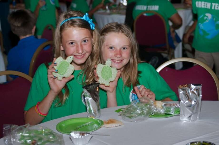 Avery Feagin and Emily Short enjoy turtle shaped cookies served during a ceremony honoring the Oppe Elementary fourth grade Green Team after school program for petitioning state legislators to make the Kemp's Ridley Sea Turtle the official state turtle of Texas Wednesday, May 29. Photo: Kirk Sides