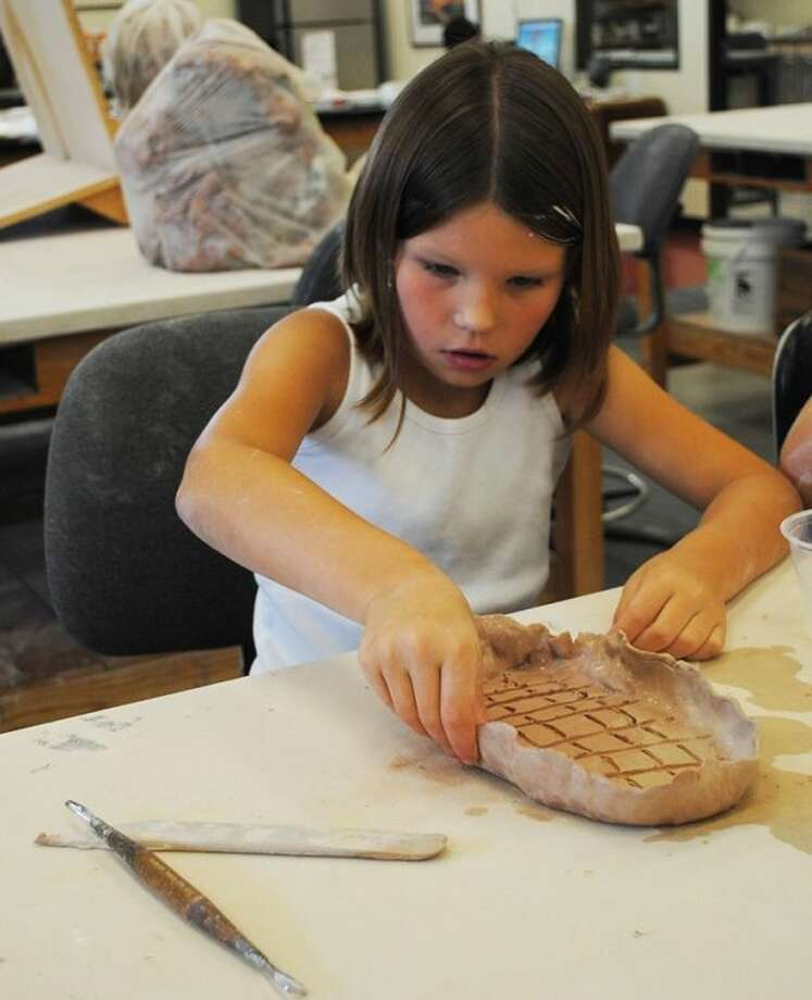 A young girl sculpts with a piece of clay during a kids summer pottery workshop in June 2012. Photo: Courtesy ACC
