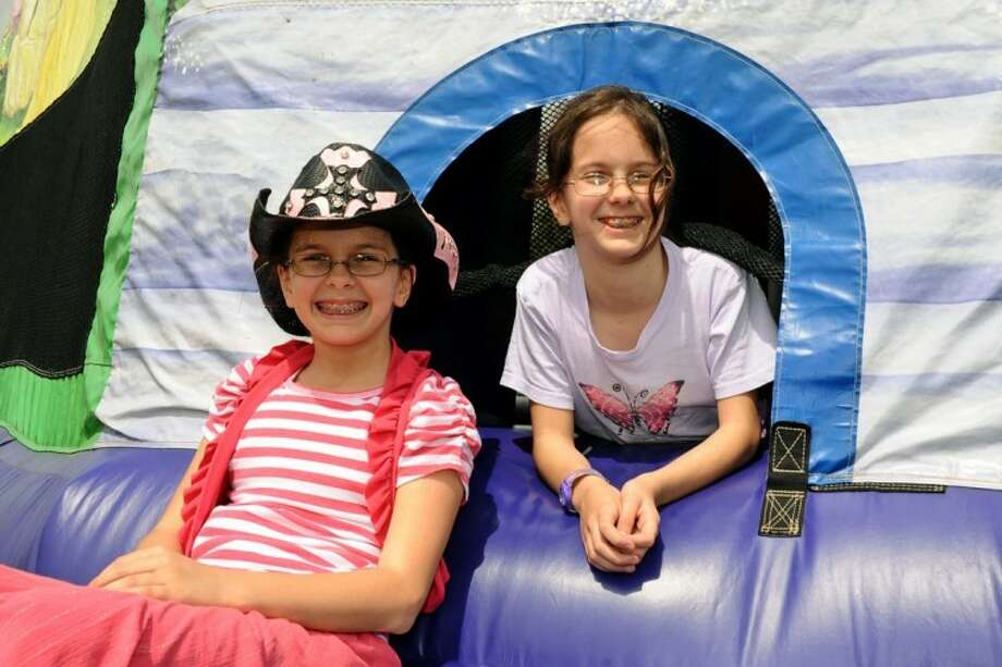 Twin sisters Faith Dickey and Grace Dickey pose for a photo during the family carnival event that they inspired to raise money for Family Promise of Clear Creek and Covenant House of Houston Saturday, Mar. 17