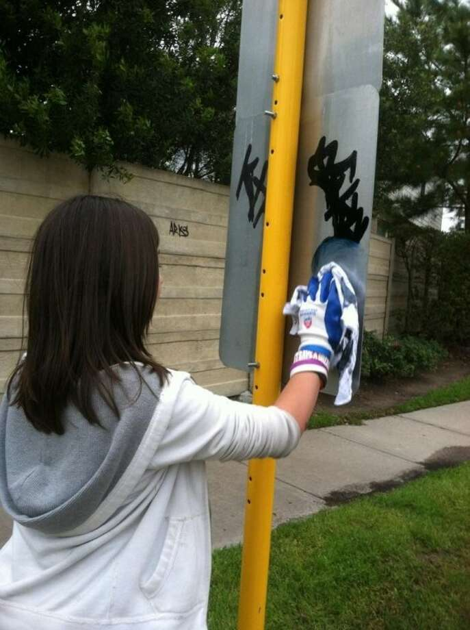 Desiree Amstutz, a former Kings Manor Elementary student, cleans up around her neighborhood and the areas around the school to rid them of graffiti during her spring break vacation.