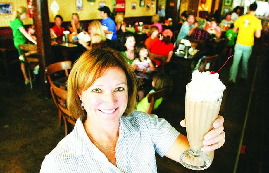 Renee Butler, owner of Another Time Soda Fountain , shows off an ice cream soda .