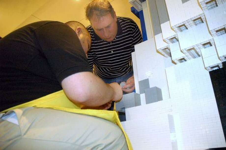Steininger and a Lego employee make a minor repair to the large R2D2.