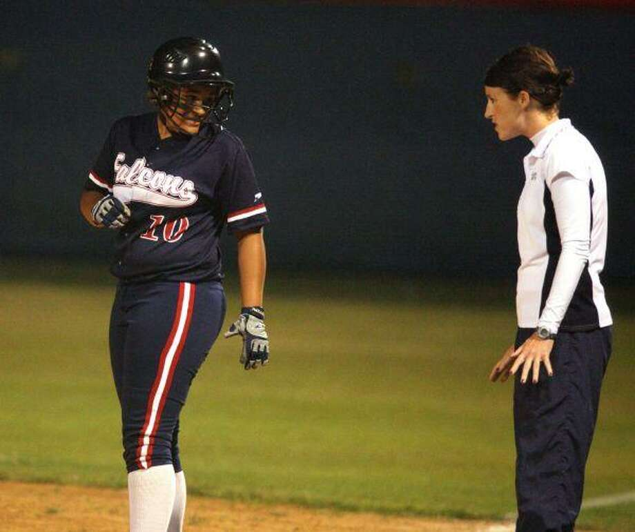 Following her single, Allyson Johnson gets instructions from the coach at first base.