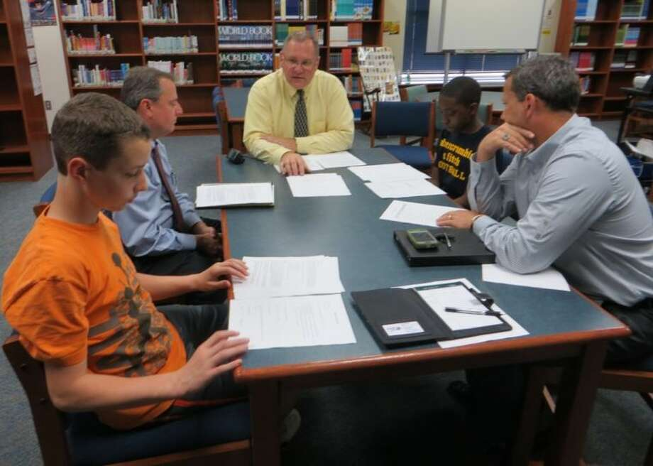 Keith Fickel, Associate Principal at Baines (clockwise from top) leads program participants in an introductory meeting.