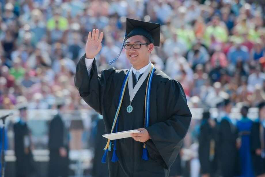 Ben Sun waves to the crowd after he receives his diploma during the Clear Springs High School commencement ceremony Saturday, Jun. 8. Photo: Kirk Sides