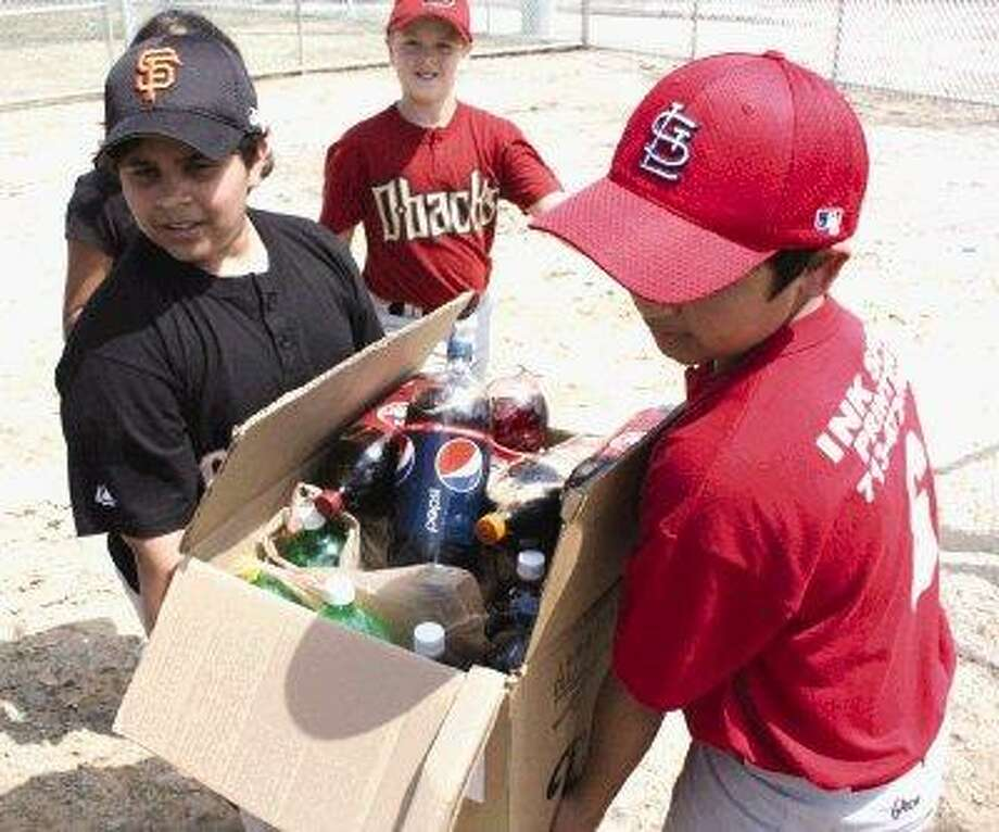 Two Pasadena Little League players carry more prizes for the ring-toss game, a traditional sight on opening day at any youth ballpark in America. Kids toss rings at bottles of soda, hoping to land one on a bottle, getting that soda as a prize. / @WireImgId=1240977