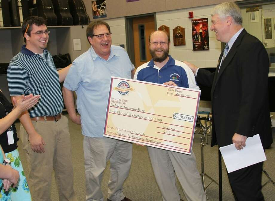 Pasadena ISD Superintendent Dr. Kirk Lewis (right) presents a 5,000 mini-grant check to Jackson Intermediate music teachers (left to right) Bradley Jacob, Allen Grubbs and Anthony Cesario. The mini-grant, sponsored by Albemarle Corp., officially pushed Pasadena ISD Education Foundation mini-grants, since 2003, over the 1 million mark.