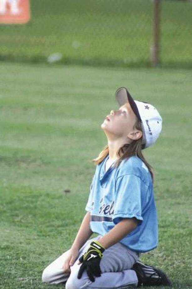 Deer Park Little League right fielder Gabriel Goudeau watches a plane fly overhead as he waits for the umpires and coaches to end a lengthy meeting at home plate during a District 17 game in the 8-year-old pitching machine tournament last week. Photo: Photo By Robert Avery