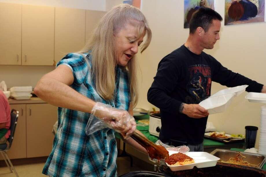 Kim Guthrie fills a plate during the Annual Senior Center Spaghetti Dinner fund raiser benefiting the Activity Center Thursday, Mar. 15.