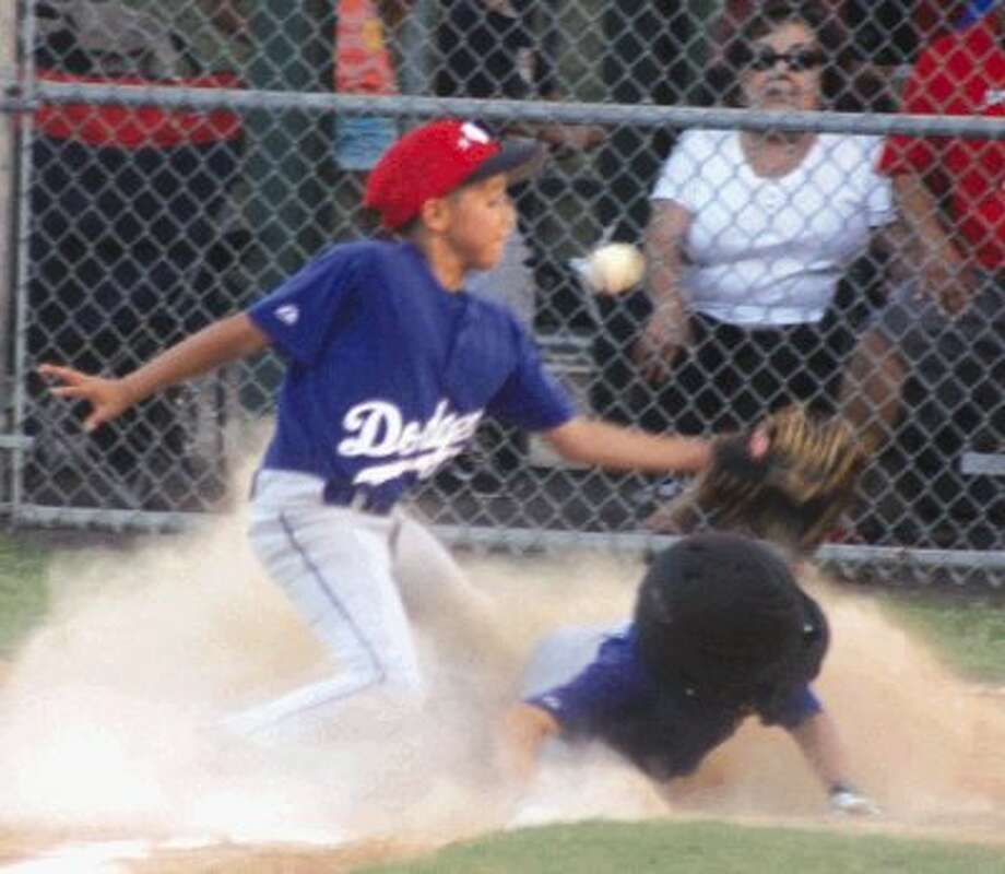 Pasadena Little League 9-year-old all-star Alex Pacheco-Lathe slides home in a cloud of dust, taking advantage of a wild pitch during a four-run third frame. But it was the only inning that the city's kids scored as North Channel Little League claimed the 9-year-old live arm District 17 championship banner. Photo: Photo By Robert Avery