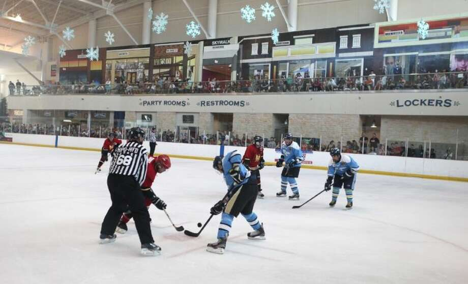 A large crowd watches the Houston Enforcers Hockey Club battle the Houston Fire Department during the inaugural 51/68 First Responder Memorial Cup at Ice Skate USA in Memorial City Mall. All proceeds from the hockey game will go directly to help the firefighters and families affected by the tragic fire on May 31. Photo: Alan Warren