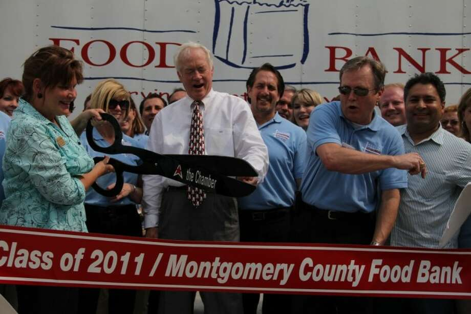 Doris Golemon, left, with the help of County Judge Alan B. Sadler, center, and the 2011 class of Leadership Montgomery County celebrate the expansion of the Montgomery County Food Bank Thursday.