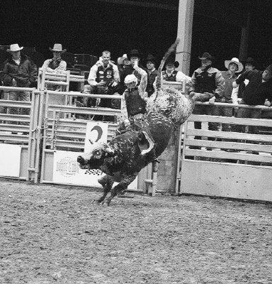A cowboy holds on as tight as he can on a bull at the Humble Rodeo and Concert Feb. 12 and 13. / @WireImgId=1244831