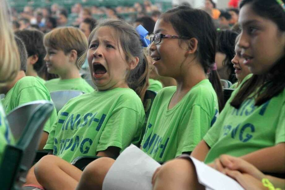 Buckalew Elementary fourth-grader Camille Gustitis reacts as the orchestra plays a section of music during Fine Arts Education Day at The Cynthia Woods Mitchell Pavilion Tuesday. More than 5,000 students gathered to learn about orchestra, music and instruments.