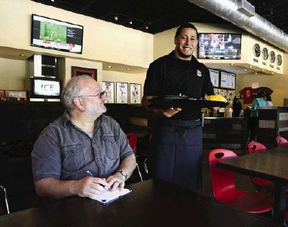 Taco USA staffer Angel Guzman delivers lunch at the restaurant's location in Grogan's Mill Village Center.