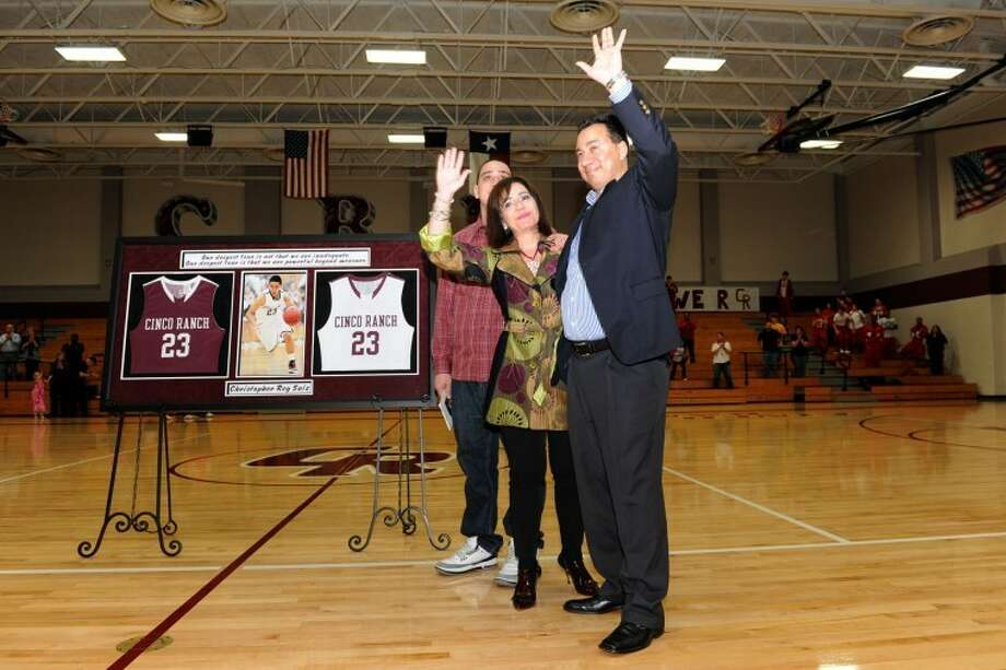 Chris Saiz's family stands next to his jersey during halftime of the Cinco Ranch boys basketball game against Katy on Tuesday night. Saiz, who died in a car accident in December, had his jersey No. 23 retired.