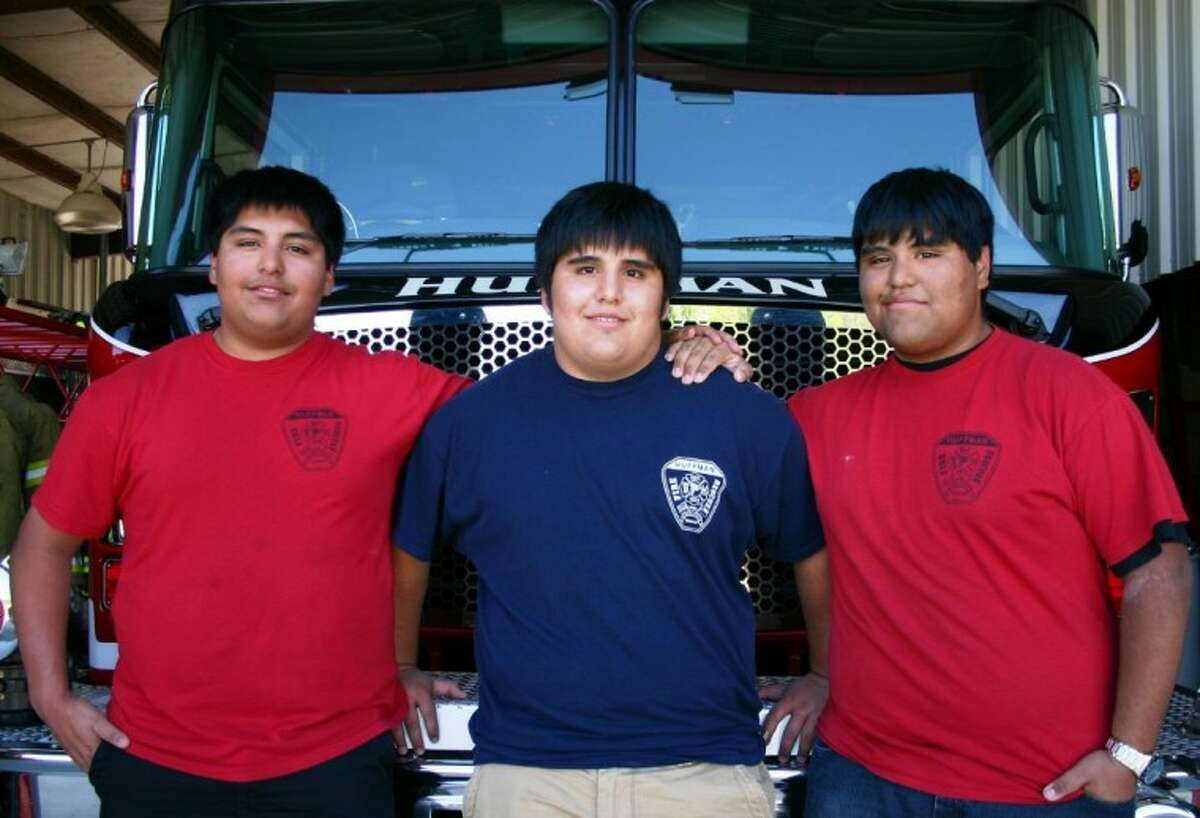 Bookend twin brothers Aguilar, Manny, left, and Robby, accompany their younger brother, Chris, to the Huffman Volunteer Fire Department station on March 21, where Chris hopes to volunteer again after doctors give him the go-ahead. A Hargrave High School EKG conducted before the school year showed the family that Chris, a sophomore who plays on the football team, had a heart abnormality. He underwent surgery March 19 to correct it.