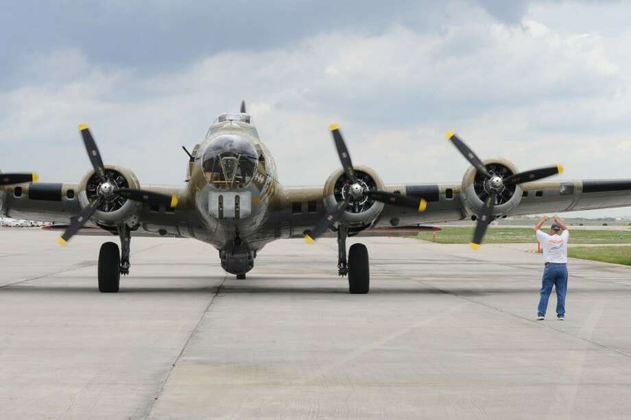 Rick Harris guides a WWII era B-17 bomber into position on the runway at Ellington Airport as the vintage aircraft arrive for the national Wings of Freedom tour Mar 28-30. Photo by KIRK SIDES