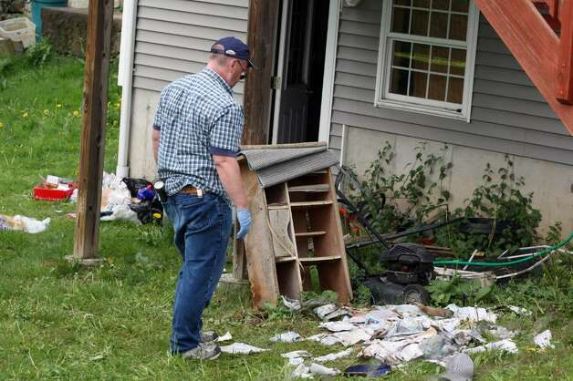 SHELTON, CT - MAY 4:   An investigator looks over a pile of mail and personnel belongings in the rear of a former home, which was forclosed on, owned by Faisal Shahzad May 4, 2010 in Shelton, Connecticut. Shahzad, a suspect in this past weekends failed bomb plot in New York City's Times Square was taken into custody late Monday by FBI agents and New York Police Department detectives while trying to leave the country.  (Photo by Daniel Barry/Getty Images)) Photo: Daniel Barry, Getty Images / 2010 Getty Images