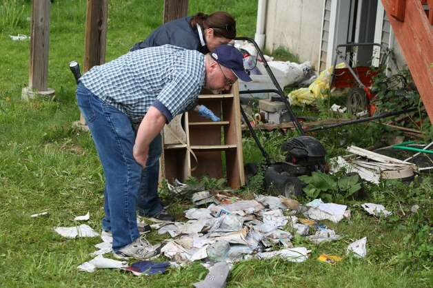 SHELTON, CT - MAY 4:   Investigators looks over a pile of mail and personal belongings in the rear of a former home, which was foreclosed upon, owned by Faisal Shahzad May 4, 2010 in Shelton, Connecticut. Shahzad, a suspect in this past weekend's failed bomb plot in New York City's Times Square, was taken into custody late Monday by FBI agents and New York Police Department detectives while trying to leave the country.  (Photo by Daniel Barry/Getty Images) Photo: Daniel Barry, Getty Images / 2010 Getty Images