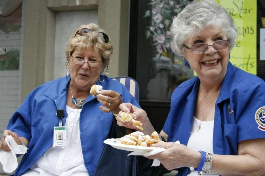 A couple of Memorial Hermann Northeast Hospital volunteers including Barbara Garland and a friend enjoy funnel cake at a past Good Oil Days. This year's festival is set for April 6.