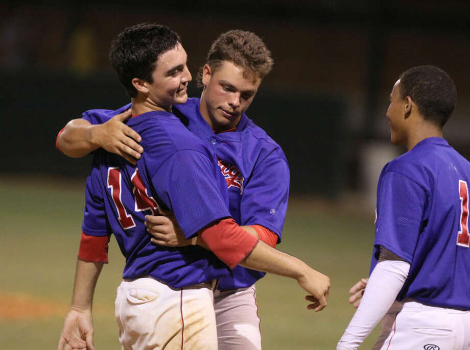 Dulles pitcher Nick Hernandez gets hugged by Dakota Mills as Josh Austin joins the celebration after the Vikings' 6-1 win against Cypress Ranch in game one of their Region III-5A semifinal series at Katy High School. Dulles will play Jersey Village for the regional championship at 8 p.m. May 31 at the University of Houston. Visit www.hcnpics.com for more photos.