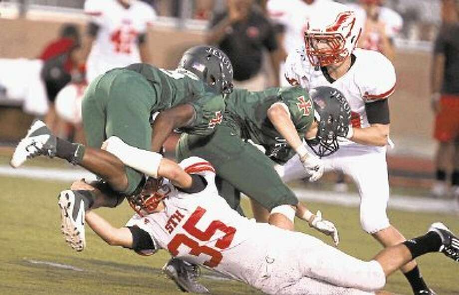 Strake Jesuit's Zack Mullins, shown here last year picking up yardage against St. Thomas, and the rest of the Crusaders recently completed their spring football workouts as they look to turn around last year's 2-8 season. Mullins was one of many young players that saw action last year for Strake Jesuit and Clancy said all of those guys had spring sessions. Photo: Photo By Alan Warren / @WireImgId=2611664