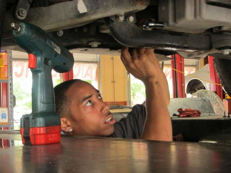 Auto Max Automotive service manager T.J. Denmon works on an oil change last week at the Missouri City location.