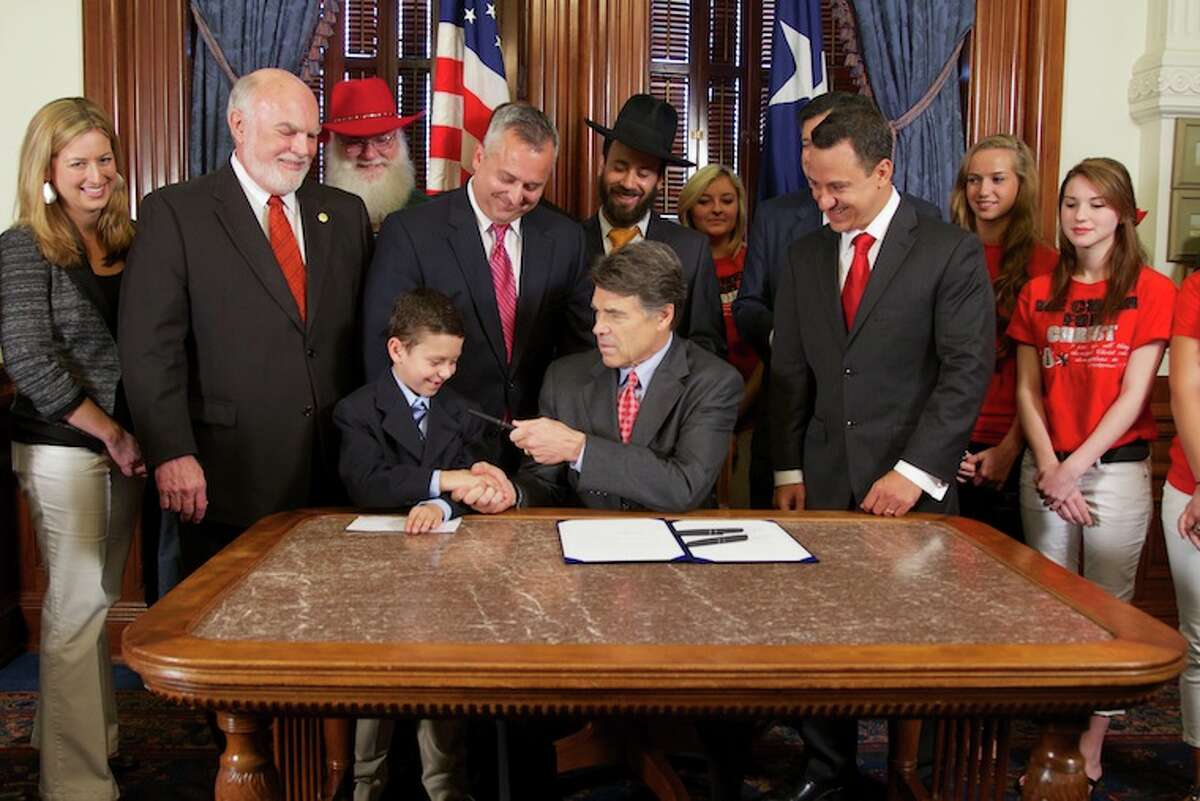 Gov. Rick Perry, center, signs the Religions Freedoms Bill at a ceremony Thursday.