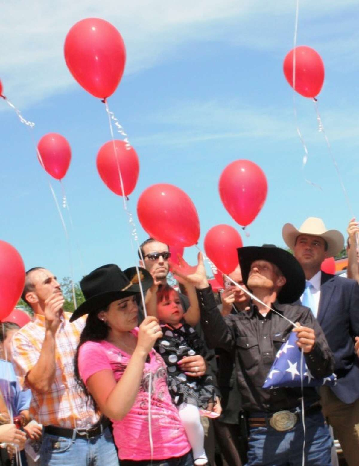 Mike and April Davis and their daughter, Abbygail, release balloons in recognition of their son Devon, at the boy's funeral on Friday, April 6, at Cornerstone Church of Cleveland. Devon was missing for several days before his body was found in a nearby lake near his family's home in Sam Houston Lake Estates.