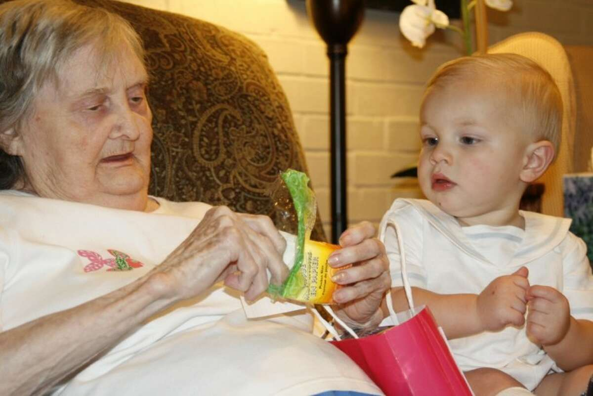 Ryan Melton, right, spends time with a 'grandma' at Unlimited Care-Kingwood Cottage as a part of the Baby Buddies program his mother, Melissa Melton founded. They visited the assistance care home to pass out Easter bags to the residents April 5.