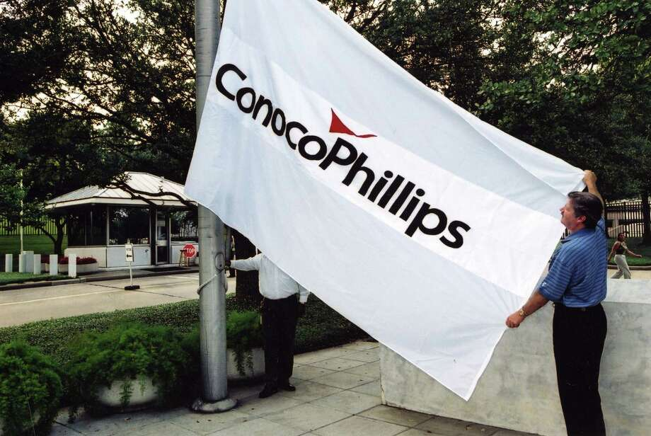A ConocoPhillips worker raises the flag at the new company's headquarters after the 2002 merger. / handout