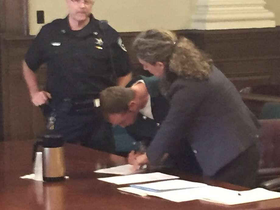 Joseph Badger signs two orders of protection to stay away from two 16-year-old girls in Troy City Court on Wednesday, Sept. 28, 2016. (Kenneth C. Crowe/Times Union)