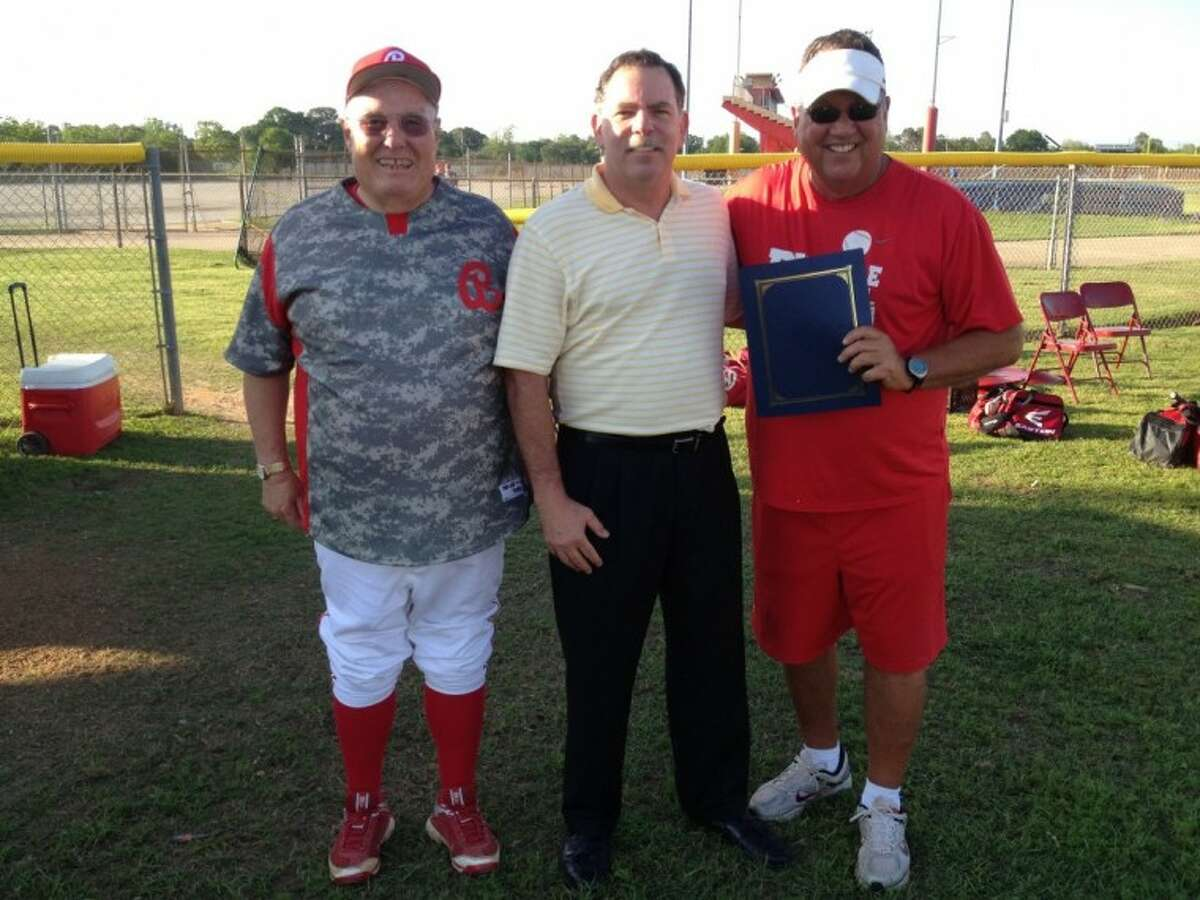 Bellaire High School baseball coaches Rocky Manuel (right) and Mike Walker (left) stand with City of Bellaire Mayor Phil Nauert following Nauert's recognition of Manuel's service to the community.