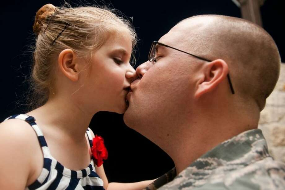 Staff Sergeant Justin Howard gives a kiss to his daughter Emily after surprising her at the Jazz Times recital held at Atascocita Community Church June 20, 2013. Photo: AMANDA J.CAIN/ The Observer