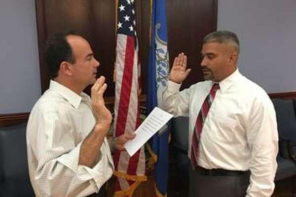 Mayor Joseph Ganim, left, swears in Rafael Fonseca as a member of the Board of Education in Bridgeport.