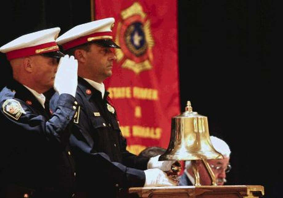 East Montgomery County Fire Department Honor Guard members Stuart Norman, right, and James Wathen take part in the ceremonial final alarm Sunday, June 23, 2013 during a memorial service honoring firefighters who have passed away in the past year and those that have died in the line of duty at The Woodlands Waterway Marriott in The Woodlands, Texas. The memorial service was part of the State Firemen's and Fire Marshal's Association of Texas' 137th Annual Training and Conference and Convention. (AP Photo/The Courier, Eric S. Swist) / AP