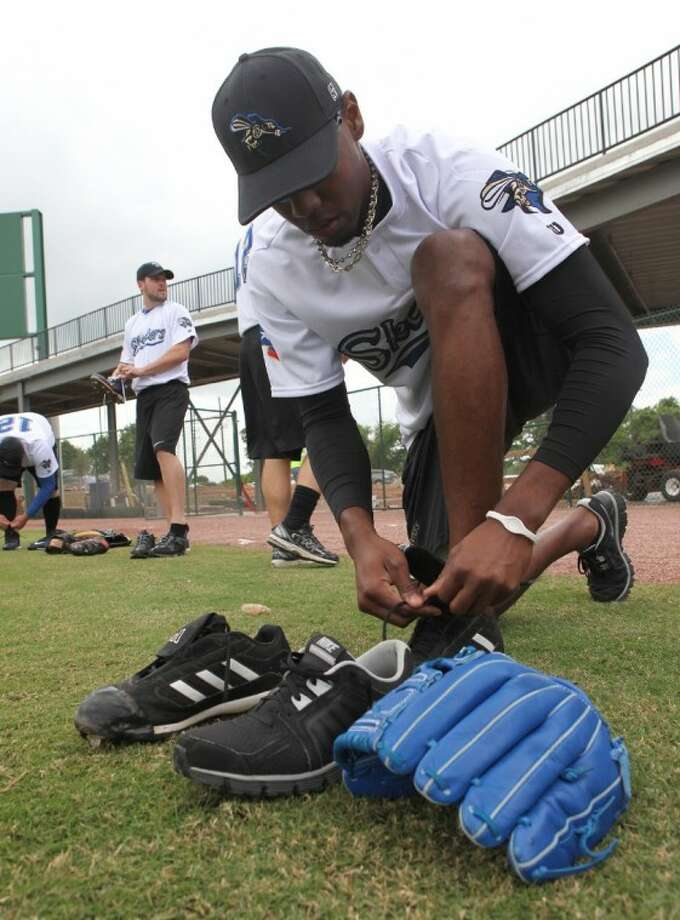 Skeeter Duniesky Flores from Cuba, ties up his laces as he gets ready to practice at Constellation Field in Sugar Land on Friday, April 13, 2012. (Photo by Alan Warren) Photo: Photo By Alan Warren