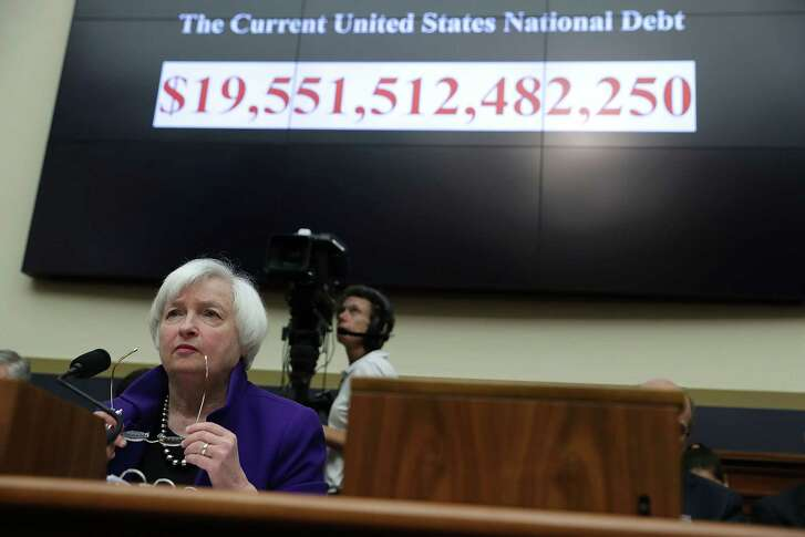 With the size of the current U.S. national debt is displayed behind her, Federal Reserve Board Chair Janet Yellen testifies during a hearing Wednesday before the House Financial Services Committee.