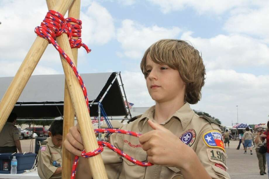 Noah Goodin 12, of Troop 1907 Fairfield Baptist Church ties off a tripod lashing at the Boy Scouts of America Scout Fair at Reliant Arena Saturday. Photo: ALAN WARREN